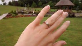 Anello di fidanzamento su un fondo dell'erba verde della mano Immagini Stock Libere da Diritti