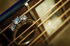Anello di fidanzamento sulle punture della chitarra Fotografia Stock Libera da Diritti
