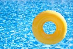 Anello di galleggiamento sullo swimpool dell'acqua blu con la riflessione delle onde fotografia stock