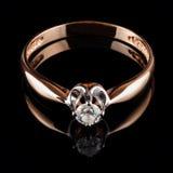 Anello dorato con il diamante isolato sul nero Immagini Stock