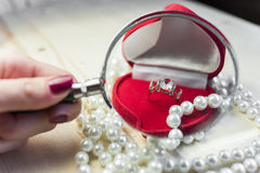 Anello dorato con topazio in un contenitore di regalo rosso con le perle sull'orlo della tavola Immagine Stock