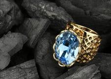 Anello dorato dei gioielli con la grande pietra preziosa sul fondo scuro del carbone Fotografia Stock