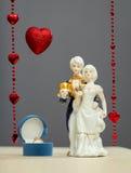 Anello dorato in scatola per le figure di giorno e della porcellana di biglietti di S. Valentino del ragazzo e della ragazza Fotografia Stock Libera da Diritti