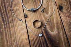 Anello e braccialetto ed orecchini e catena con il pendente su fondo di legno immagini stock libere da diritti