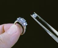 Anello e pietra di diamante della holding della mano con le pinzette Immagini Stock Libere da Diritti