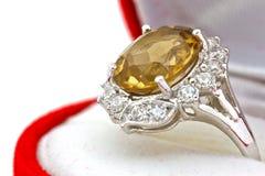 Anello giallo dello zaffiro su fondo isolato bianco Fotografia Stock