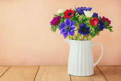 Anemone flowers in white vase on wooden table Royalty Free Stock Photos