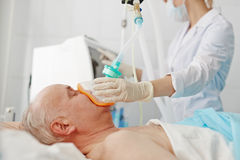 Anesthesia before operation. Doctor applying oxygen mask on senior patient Stock Photo
