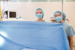 Anesthesiologist at Work. Anesthesiologist standing behind curtain in operating theater Stock Photos
