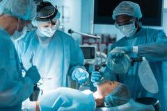 anesthetist d'afro-américain tenant le masque à oxygène au-dessus du patient images stock
