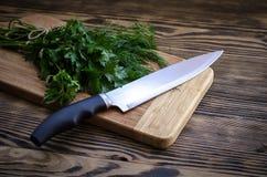 Aneto e prezzemolo freschi su un tagliere con il coltello sulla tavola di legno Fotografie Stock Libere da Diritti