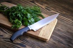 Aneto e salsa frescos em uma placa de corte com a faca na tabela de madeira Fotografia de Stock Royalty Free