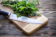 Aneto e salsa frescos em uma placa de corte com a faca na tabela de madeira Imagens de Stock Royalty Free