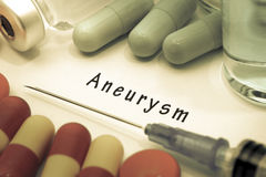 Aneurysm. Diagnosis written on a white piece of paper. Syringe and vaccine with drugs stock photo