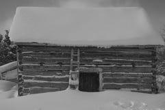 Anexo velho da cabana rústica de madeira na neve Fotografia de Stock