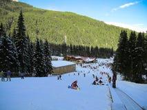 Anfängersnowboarder und -Skifahrer lernen, auf die Ausbildungssteigung zu fahren lizenzfreies stockbild