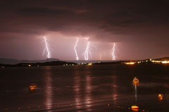 Anfang eines Sturms in einem Meer mit Blitzen im purpurroten Himmel Stockfotografie
