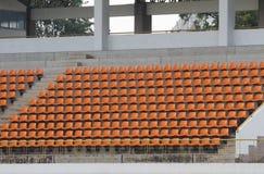 Anfiteatro de asientos anaranjados en fondo del extracto del estadio imágenes de archivo libres de regalías
