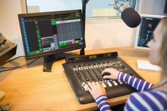 Anfitrião de rádio fêmea na frente da tela que opera o misturador sadio fotografia de stock