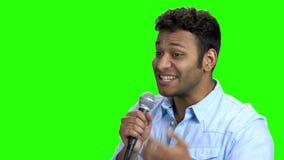 Anfitrião energético que fala no microfone na tela verde filme