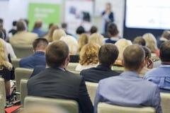 Anfitrião fêmea profissional que fala na frente da grande audiência durante a conferência de negócio imagens de stock royalty free