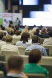 Anfitrião fêmea que fala na frente da grande audiência durante a conferência de negócio imagem de stock
