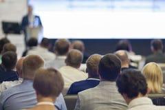 Anfitrião masculino profissional que fala na frente da audiência durante a conferência de negócio foto de stock