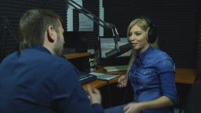Anfitrión de radio contento atractivo que se entrevista con a una huésped en estudio almacen de video