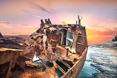 Anfrätt metallskepp på det blåa havsvattnet på solnedgången Arkivfoto