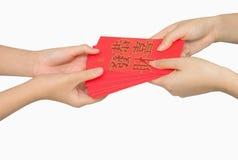 ANG εκμετάλλευσης χεριών pow ή κόκκινο δώρο χρημάτων πακέτων Στοκ Φωτογραφία