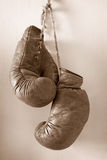 Ang up the gloves, old worn boxing gloves. Hang up the gloves, old worn leather boxing gloves in sepia tones, hanging on grunge style wall stock photos
