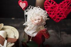 Ange blanc de l'amour sur un cheval rouge et avec un coeur dans sa main Photo stock