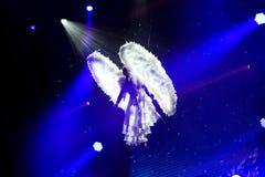 Ange blanc sur les projecteurs bleus de fond, représentation gymnastique aérienne, artiste de cirque Photos stock