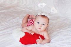 Ange de bébé se trouvant sur la couverture molle blanche Image libre de droits