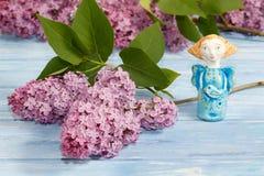 Ange de poterie d'argile et des branches de lilas sur le conseil en bois bleu Images libres de droits