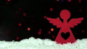 Ange en bois rouge de décoration de Noël sur la neige au-dessus des lumières blured de bokeh sur le fond banque de vidéos
