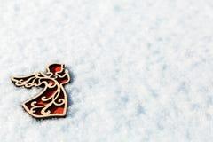 Ange en bois rouge de jouet sur la neige Photos libres de droits