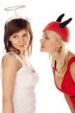Ange et filles de diable au-dessus de blanc Photographie stock