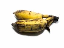 Angebaute Banane auf dem weißen lokalisierten u. Abschneidenteil des Hintergrundes Die gelbliche und schwarze Farbe wird durch di Stockbilder