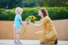 Angebotbündel des kleinen Jungen Sonnenblumen zu seiner Mutter Lizenzfreie Stockfotografie