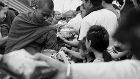 Angebote in der Almosenschüssel eines Mönchs Stockbild