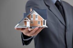 Grundstücksmakler mit Haus Stockbild