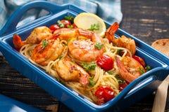 angebratene Spaghettis mit gegrillten Garnelen und Tomaten - italienische Fusionsnahrungsmittelart lizenzfreie stockfotos