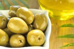 Angefüllte grüne Oliven und Olivenölmakro Stockfoto