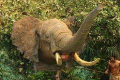 Angefüllter afrikanischer Elefant gegen lebensechten Dschungel mit Jäger Stockfoto