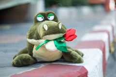 Angefüllter Alligator, der Rosen hält Stockbild