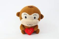 Angefüllter brauner Affe, der ein rotes Herz hält Stockbild