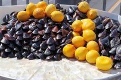 Angefüllter Miesmuschel-Korb und Zitrone stockbilder