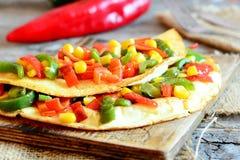 Angefülltes Omelett auf einem hölzernen Brett Gesundes gebratenes Omelett angefüllt mit rotem und grünem grünem Pfeffer und Mais  Stockbilder