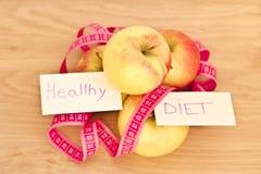 Angehäufte Äpfel und messendes Band: Essen gesund Stockfotografie